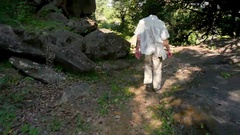 Man walks along a mountain path in Sunny day Stock Footage