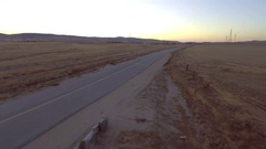 Aerial View of long road in desert at golden hour Stock Footage
