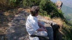 Man sits in meditation in the mountains Stock Footage