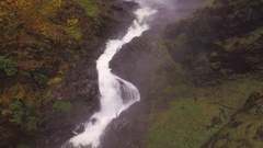 Bottom of Waterfall Flows into River with Misty Water Drops Stock Footage