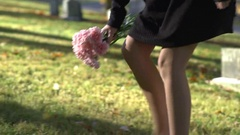 Girl walks up to grave and drops off flowers 4k Stock Footage