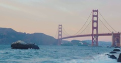 Golden gate bridge by Baker beach with a beautiful sunset and a crossing ship Stock Footage