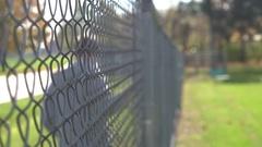 Man walking by fence dragging fingers across mesh 4k Stock Footage