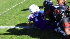Helmets hit as runner is tackled out of bounds in youth football game 3763 Stock Footage