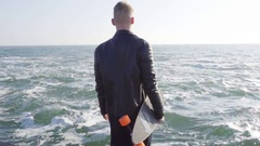 Young man in black leather jacket holds his longboard by the sea Stock Footage