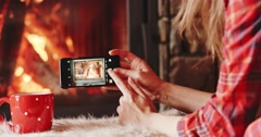Woman Hands Taking Picture on Phone by the Burning Fireplace. 4K SLOW MOTION Stock Footage