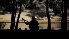 Man playing guitarin front of the Sun-set silhouette Arkistovideo