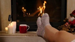 Woman is sitting with cup of hot drink and book near the fireplace Stock Footage