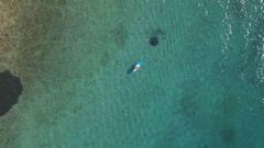AERIAL: Woman supping near coast in crystal clear ocean with visible sea bottom Stock Footage