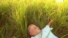 Funny little boy lying in green grass and smiling. Stock Footage
