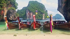 Thai Longtail Boats in Shallow Sea by Beach against Green Cliffs Stock Footage