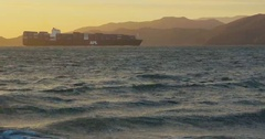 Big cargo ship with containers entering harbor by the sunset at the sea Stock Footage