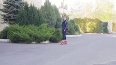Cool young man in leather jacket skating on his longboard Stock Footage