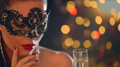 Beautiful woman wearing venetian masquerade mask at party drinking champagne. Stock Footage