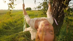 Young woman on a swing in the summer evening Stock Footage
