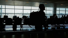 A large airport terminal on a sunny day. Silhouettes of people waiting for a Stock Footage