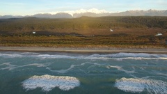Aerial view of surfing waves on beach and snowy mountains Stock Footage