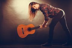 Rock musician destroys his guitar. Stock Photos
