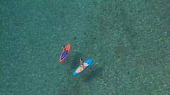 AERIAL: Two friends stand up paddle boarding in amazing crystal clear ocean Stock Footage