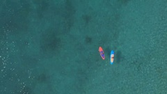 AERIAL: Sporty female riders paddleboarding in amazing crystal clear tropic sea Stock Footage