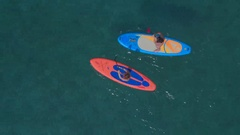 AERIAL, CLOSE UP: Girls stand up paddle boarding in parallel, paddling in rhythm Stock Footage