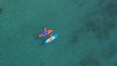 AERIAL: Women having fun, competing and stand up paddle boarding in deep ocean Stock Footage