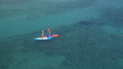 AERIAL: Two girls hanging out, relaxing and having fun standup paddleboarding Stock Footage