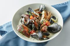 Serving of fresh cooked blue mussels in plate Stock Photos