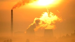 Cityscape urban landscape factory and large pipes smoke at sunrise sun shining Stock Footage