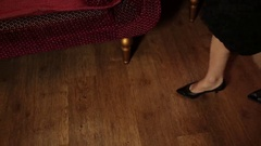 Young woman undressing near the couch, close-up long legs Stock Footage