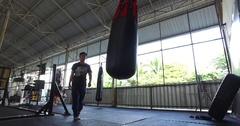 Asian man does Muay Thai on punch bag with kick in gym Stock Footage