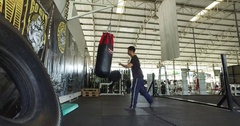 Low angle Asian man in gym Muay Thai punching bag with spin kick Stock Footage