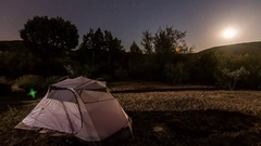 Moon rising above a tent Stock Footage