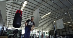 Low angle Asian man in gym kicking and punching bag Muay Thai training Stock Footage
