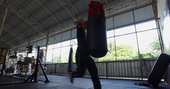 Asian man does Muay Thai on punch bag with elbow in gym Stock Footage