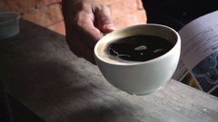 A man drinking a cup of hot black coffee (americano) , slow motion Stock Footage