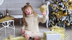 Emotional little girl holds a gift box in hands, try to open near Christmas tree Stock Footage