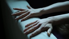 Close-up hands of a young woman lying on a bad. Girl crumples upholstery couch Stock Footage