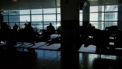 Passengers sit in a waiting airplane flight. People walk by, see the silhouettes Stock Footage