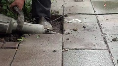 An operator is using a jackhammer to lift floor tiles and bricks. Stock Footage