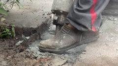 A worker is breaking with a jackhammer the concrete in the ground. Stock Footage