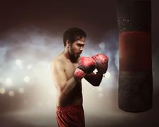 Masculine asian boxer man exercising with punching bag Stock Photos