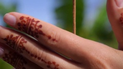Hand with Henna Tattoo Touching Incense Stick Stock Footage