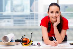 Young woman in coveralls doing repairs Stock Photos