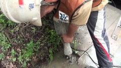 A operator is using a jackhammer to break the ground and discover a water leak. Stock Footage