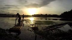Boatman maneuvers his boat on lake at sundown. silhouettes Stock Footage
