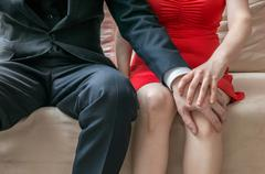 Harassment at workplace. Manager is touching knee of his secretary. Stock Photos