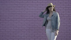 Young Woman With A Hat Poses In Front Of Pink Brick Wall Stock Footage