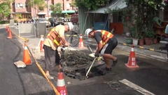 Workers are repairing a leak on a road. They are working with hammers. Stock Footage