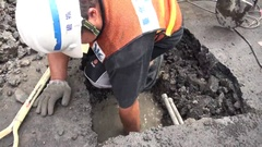 A worker is discovering with his hand a pipe in a water leak. Stock Footage